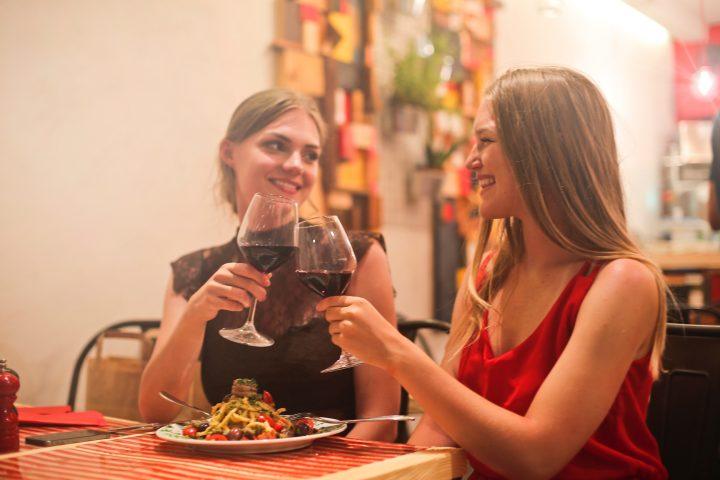 Femei ciocnind un pahar de vin peste paste