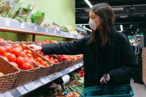 Femei cu mască făcnd cumpărături în timpul pandemiei